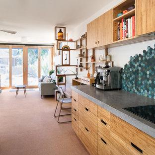 Diseño de cocina en U, actual, de tamaño medio, abierta, con fregadero bajoencimera, armarios con paneles lisos, puertas de armario de madera clara, encimera de cemento, salpicadero gris, salpicadero de azulejos de piedra, suelo de corcho, una isla y suelo beige