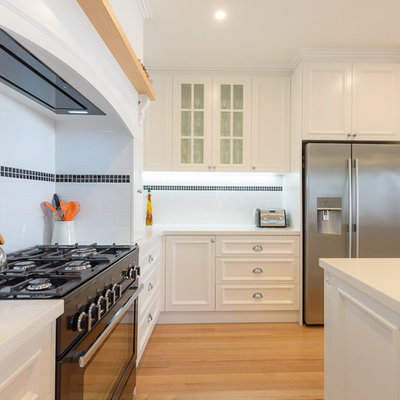 Open concept kitchen - large traditional l-shaped light wood floor open concept kitchen idea in Melbourne with an undermount sink, recessed-panel cabinets, white cabinets, quartz countertops, white backsplash, subway tile backsplash, black appliances and an island
