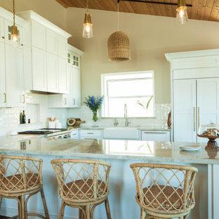 サンルイスオビスポの大きいビーチスタイルのおしゃれなキッチン (シングルシンク、シェーカースタイル扉のキャビネット、白いキャビネット、珪岩カウンター、ベージュキッチンパネル、セラミックタイルのキッチンパネル、シルバーの調理設備の、濃色無垢フローリング、茶色い床、ベージュのキッチンカウンター) の写真