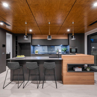 Contemporary galley kitchen in Canberra - Queanbeyan with a drop-in sink, flat-panel cabinets, grey cabinets, blue splashback, stainless steel appliances, with island, grey floor and grey benchtop.