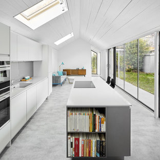 Photo of a contemporary open plan kitchen in Edinburgh with a single-bowl sink, flat-panel cabinets, white cabinets, grey splashback, an island, grey floors and white worktops.