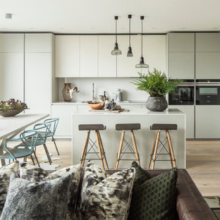 Design ideas for a contemporary open plan kitchen in London with flat-panel cabinets, white cabinets, white splashback, black appliances, light hardwood flooring, an island and white worktops.