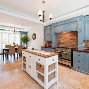 ロンドンのヴィクトリアン調のおしゃれなダイニングキッチン (落し込みパネル扉のキャビネット、青いキャビネット、木材カウンター) の写真