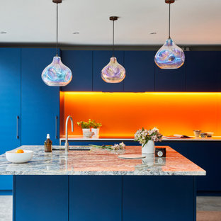 Large contemporary l-shaped kitchen/diner in London with flat-panel cabinets, blue cabinets, quartz worktops, orange splashback, glass sheet splashback, stainless steel appliances, concrete flooring, an island and grey floors.