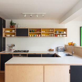 Bild på ett mellanstort 60 tals vit vitt u-kök, med en undermonterad diskho, släta luckor, rostfria vitvaror, orange golv, svarta skåp och en halv köksö