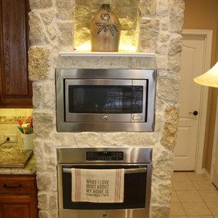 ダラスの大きいラスティックスタイルのおしゃれなキッチン (ドロップインシンク、シェーカースタイル扉のキャビネット、中間色木目調キャビネット、御影石カウンター、ベージュキッチンパネル、石タイルのキッチンパネル、シルバーの調理設備の、磁器タイルの床) の写真