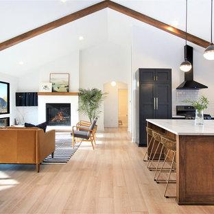 グランドラピッズの大きい北欧スタイルのおしゃれなキッチン (エプロンフロントシンク、シェーカースタイル扉のキャビネット、青いキャビネット、珪岩カウンター、白いキッチンパネル、サブウェイタイルのキッチンパネル、黒い調理設備、淡色無垢フローリング、ベージュの床、白いキッチンカウンター) の写真
