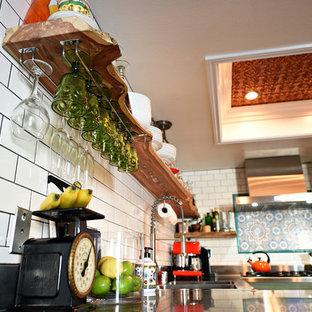 Mittelgroße Stilmix Wohnküche ohne Insel in U-Form mit integriertem Waschbecken, flächenbündigen Schrankfronten, grünen Schränken, Edelstahl-Arbeitsplatte, Küchenrückwand in Weiß, Rückwand aus Keramikfliesen, Küchengeräten aus Edelstahl und Porzellan-Bodenfliesen in Las Vegas