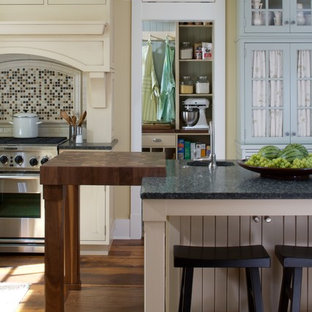 Elegant kitchen photo in Grand Rapids with wood countertops