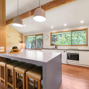 Photo of a beach style kitchen in Melbourne with a single-bowl sink, flat-panel cabinets, white cabinets, white appliances, medium hardwood floors, with island, grey benchtop and exposed beam.