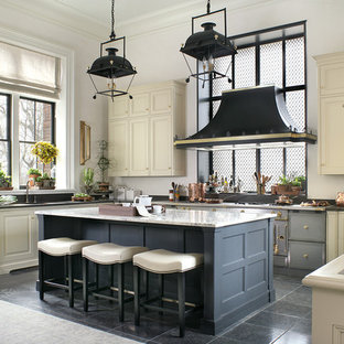 Photo of a large traditional u-shaped kitchen in New York with recessed-panel cabinets, beige cabinets, granite benchtops, coloured appliances, limestone floors and with island.