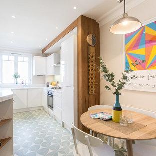 На фото: п-образные кухни в скандинавском стиле с обеденным столом, плоскими фасадами, белыми фасадами и зеленым полом без острова