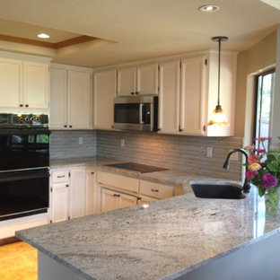 Inspiration for a small beach style u-shaped eat-in kitchen in Sacramento with recessed-panel cabinets, white cabinets, granite benchtops, grey splashback, glass sheet splashback, stainless steel appliances, an undermount sink and ceramic floors.
