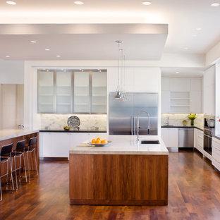 オースティンの広いコンテンポラリースタイルのおしゃれなキッチン (一体型シンク、ガラス扉のキャビネット、ステンレスキャビネット、白いキッチンパネル、石タイルのキッチンパネル、シルバーの調理設備、濃色無垢フローリング、大理石カウンター、茶色い床) の写真