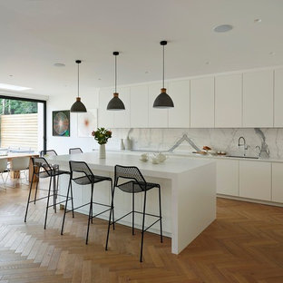 Photo of a contemporary kitchen/diner in London with a submerged sink, flat-panel cabinets, white cabinets, white splashback, marble splashback, light hardwood flooring, an island and beige floors.