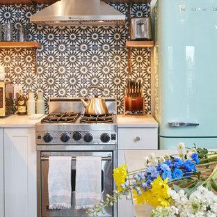 ニューヨークの中くらいのエクレクティックスタイルのおしゃれなキッチン (エプロンフロントシンク、シェーカースタイル扉のキャビネット、白いキャビネット、クオーツストーンカウンター、マルチカラーのキッチンパネル、セメントタイルのキッチンパネル、シルバーの調理設備、無垢フローリング、茶色い床、グレーのキッチンカウンター) の写真