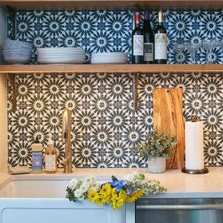 ニューヨークの中サイズのエクレクティックスタイルのおしゃれなキッチン (エプロンフロントシンク、シェーカースタイル扉のキャビネット、白いキャビネット、クオーツストーンカウンター、マルチカラーのキッチンパネル、セメントタイルのキッチンパネル、シルバーの調理設備の、無垢フローリング、茶色い床、グレーのキッチンカウンター) の写真