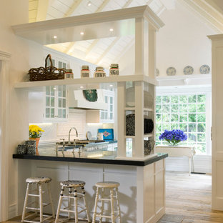 Example of a classic kitchen design in Denver with glass-front cabinets, white cabinets and white backsplash