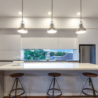Mid-sized trendy single-wall medium tone wood floor open concept kitchen photo in Brisbane with white cabinets, marble countertops, stainless steel appliances, an island, flat-panel cabinets, an undermount sink and window backsplash