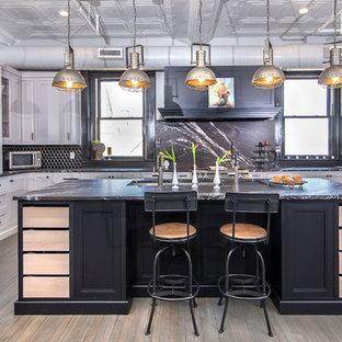 Große Industrial Küche in L-Form mit Küchenrückwand in Schwarz, Küchengeräten aus Edelstahl, schwarzer Arbeitsplatte, Unterbauwaschbecken, Schrankfronten mit vertiefter Füllung, weißen Schränken, dunklem Holzboden, Kücheninsel und braunem Boden in Charlotte