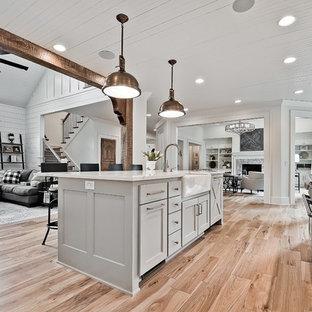 Idéer för ett stort amerikanskt vit kök med öppen planlösning, med en rustik diskho, luckor med upphöjd panel, vita skåp, bänkskiva i kvarts, vitt stänkskydd, stänkskydd i stenkakel, rostfria vitvaror, ljust trägolv, en köksö och brunt golv