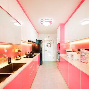 Zweizeilige Moderne Küche ohne Insel mit Doppelwaschbecken, flächenbündigen Schrankfronten, Küchenrückwand in Rosa, Glasrückwand und schwarzen Elektrogeräten in Singapur