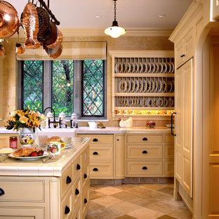 Idéer för mellanstora vintage beige kök, med en rustik diskho, luckor med profilerade fronter, skåp i ljust trä, kaklad bänkskiva, beige stänkskydd, stänkskydd i kalk, integrerade vitvaror, travertin golv, en köksö och beiget golv