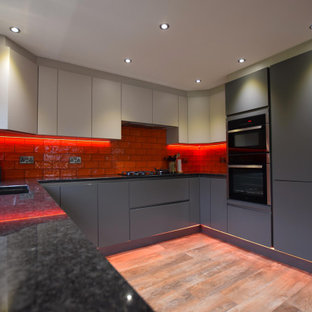 Design ideas for a medium sized contemporary u-shaped kitchen in Other with a submerged sink, flat-panel cabinets, grey cabinets, red splashback, metro tiled splashback, no island, brown floors and black worktops.