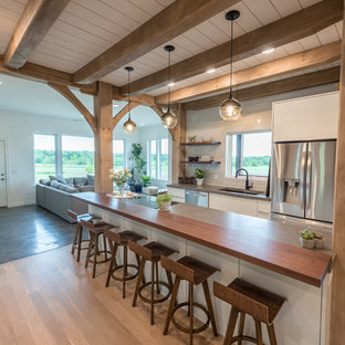Mid-sized farmhouse open concept kitchen designs - Open concept kitchen - mid-sized farmhouse single-wall medium tone wood floor and brown floor open concept kitchen idea in Minneapolis with an undermount sink, flat-panel cabinets, white cabinets, concrete countertops, white backsplash, subway tile backsplash, stainless steel appliances, an island and gray countertops