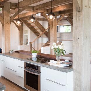 ミネアポリスの中サイズのカントリー風おしゃれなキッチン (アンダーカウンターシンク、フラットパネル扉のキャビネット、白いキャビネット、コンクリートカウンター、白いキッチンパネル、サブウェイタイルのキッチンパネル、シルバーの調理設備、無垢フローリング、茶色い床、グレーのキッチンカウンター) の写真
