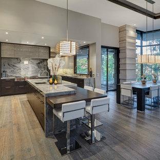 Esempio di una cucina minimal con lavello sottopiano, ante lisce, ante in legno bruno, paraspruzzi grigio, paraspruzzi in lastra di pietra, elettrodomestici in acciaio inossidabile, parquet scuro, isola, pavimento marrone e top grigio