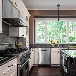Exempel på ett stort klassiskt l-kök, med en undermonterad diskho, luckor med upphöjd panel, vita skåp, granitbänkskiva, grått stänkskydd, rostfria vitvaror, mörkt trägolv, en köksö och stänkskydd i skiffer