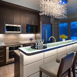Идея дизайна: большая прямая кухня в современном стиле с плоскими фасадами, техникой из нержавеющей стали, стеклянной столешницей, одинарной раковиной, темными деревянными фасадами, коричневым фартуком, фартуком из каменной плиты, полом из керамогранита и островом
