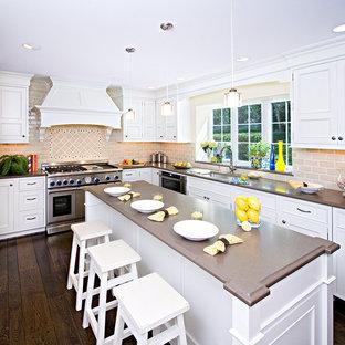 Inspiration för ett stort vintage brun brunt kök, med en undermonterad diskho, luckor med profilerade fronter, vita skåp, bänkskiva i kvarts, beige stänkskydd, stänkskydd i tunnelbanekakel, integrerade vitvaror, mörkt trägolv, en köksö och brunt golv