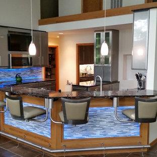 シカゴの大きいエクレクティックスタイルのおしゃれなキッチン (フラットパネル扉のキャビネット、グレーのキャビネット、御影石カウンター、グレーのキッチンパネル、ボーダータイルのキッチンパネル、シルバーの調理設備、クッションフロア、アンダーカウンターシンク、茶色い床) の写真