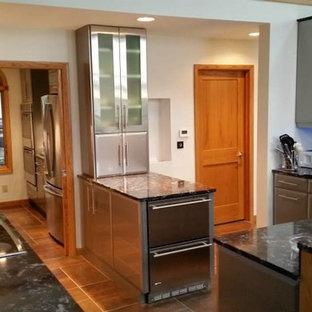 シカゴの大きいエクレクティックスタイルのおしゃれなキッチン (フラットパネル扉のキャビネット、グレーのキャビネット、御影石カウンター、アンダーカウンターシンク、グレーのキッチンパネル、ボーダータイルのキッチンパネル、シルバーの調理設備、クッションフロア、茶色い床) の写真
