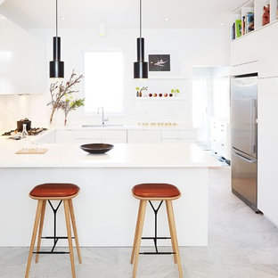 Mid-sized modern u-shaped kitchen in Toronto with flat-panel cabinets, white cabinets, solid surface benchtops, stainless steel appliances, marble floors, a double-bowl sink, white splashback, marble splashback, a peninsula and grey floor.