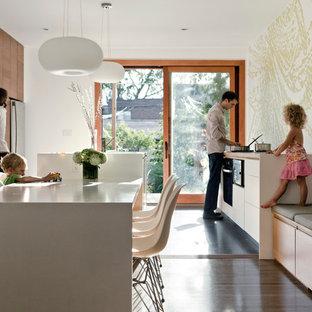 Ejemplo de cocina comedor moderna con electrodomésticos de acero inoxidable, armarios con paneles lisos y puertas de armario de madera en tonos medios