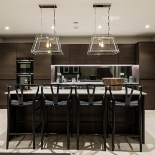 Inspiration for a large contemporary galley kitchen in London with a submerged sink, flat-panel cabinets, brown cabinets, metallic splashback, mirror splashback, stainless steel appliances, porcelain flooring, an island, beige floors and white worktops.
