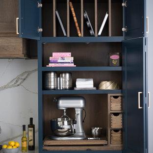 Lantlig inredning av ett mellanstort brun brunt kök, med en rustik diskho, släta luckor, blå skåp, bänkskiva i kvarts, vitt stänkskydd, stänkskydd i sten, rostfria vitvaror, mellanmörkt trägolv, en köksö och brunt golv