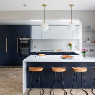 Medium sized contemporary u-shaped kitchen in London with marble worktops, white splashback, ceramic splashback, black appliances, light hardwood flooring, a breakfast bar, white worktops, flat-panel cabinets, blue cabinets and beige floors.