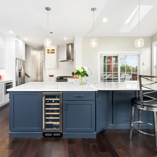 Large transitional l-shaped eat-in kitchen in Philadelphia with a farmhouse sink, shaker cabinets, white cabinets, quartz benchtops, white splashback, subway tile splashback, stainless steel appliances, dark hardwood floors, with island, brown floor and blue benchtop.