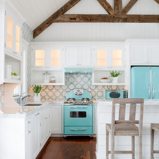 Small beach style l-shaped open plan kitchen in St Louis with white cabinets, multi-coloured splashback, coloured appliances, with island, an undermount sink, beaded inset cabinets, quartz benchtops, mosaic tile splashback and medium hardwood floors.