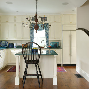 Ejemplo de cocina en L, clásica, con armarios con rebordes decorativos, puertas de armario beige, electrodomésticos de acero inoxidable, suelo de madera en tonos medios, una isla, encimera de granito y encimeras turquesas