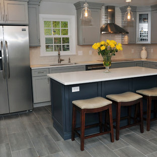 Large transitional eat-in kitchen designs - Example of a large transitional l-shaped gray floor and porcelain tile eat-in kitchen design in Philadelphia with recessed-panel cabinets, gray cabinets, white backsplash, stainless steel appliances, an island, an undermount sink, quartz countertops, ceramic backsplash and white countertops