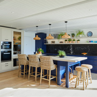 Design ideas for a medium sized nautical single-wall open plan kitchen in Kent with a submerged sink, beaded cabinets, blue cabinets, quartz worktops, black splashback, stainless steel appliances, laminate floors, an island, beige floors and black worktops.