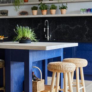 Réalisation d'une cuisine ouverte linéaire marine de taille moyenne avec un évier encastré, un placard à porte affleurante, des portes de placard bleues, un plan de travail en quartz, une crédence noire, un électroménager en acier inoxydable, sol en stratifié, un îlot central, un sol beige et un plan de travail noir.