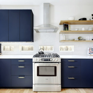 Coastal kitchen photos - Inspiration for a coastal u-shaped light wood floor kitchen remodel in Austin with flat-panel cabinets, blue cabinets, white backsplash, stainless steel appliances and white countertops