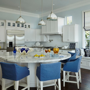 Large coastal open concept kitchen photos - Large beach style l-shaped dark wood floor and brown floor open concept kitchen photo in Miami with white backsplash, subway tile backsplash, an island, shaker cabinets, white cabinets, marble countertops and stainless steel appliances