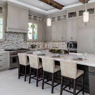 Стильный дизайн: большая угловая кухня-гостиная в стиле современная классика с врезной раковиной, фасадами в стиле шейкер, серыми фасадами, разноцветным фартуком, фартуком из удлиненной плитки, техникой под мебельный фасад, островом, столешницей из известняка, полом из керамогранита и бежевым полом - последний тренд